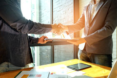 Businessmen shake hands when entering into business deal,In the. Hand are document files Stock Photo