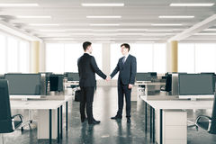 Businessmen shake hands ini modern open space office Royalty Free Stock Image