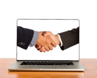Businessmen shake hands in laptop screen. Royalty Free Stock Photos