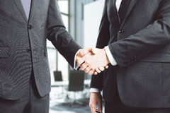 Businessmen shake hands in loft conference room Stock Image