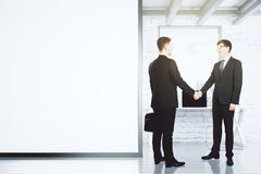 Businessmen shake hands in loft office with blank white wall, mo Stock Image