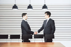 Businessmen shake hands in modern conference room with furniture Royalty Free Stock Photos