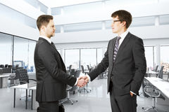 Businessmen shake hands in modern open space office Stock Photos