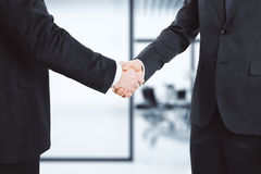 Businessmen shake hands in the office Stock Photography