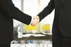 Businessmen shake hands in office Royalty Free Stock Image