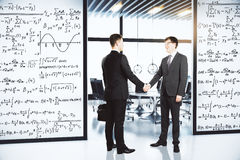 Businessmen shake hands in the office with walls with equations Royalty Free Stock Photos