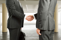Businessmen shake hands  in spacious hangar area with concrete f Stock Image