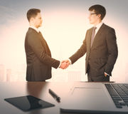 Businessmen shake hands and table withlaptop and digital tablet Royalty Free Stock Images