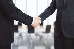 Businessmen shake their hands in conference room Stock Photo