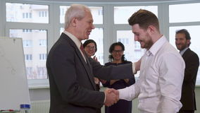 Businessmen shakes hands at the office. Two businessmen shaking their hands at the office. Senior and young men greeting each other against background of stock footage