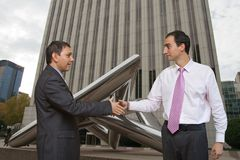 Businessmen shaking on a deal. City businessmen shaking hands in front of the Picasso building, Madrid stock photo