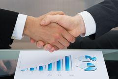 Businessmen shaking hand in front of graph Stock Photos