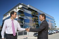 Businessmen shaking hands. Two smart businessmen shaking hands in front of a modern office building. Blue sky above Stock Photo