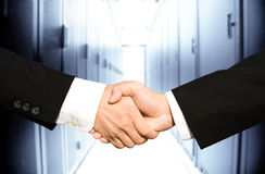 Businessmen shaking hands. Two businessmen shaking hands in a technology data center Royalty Free Stock Images