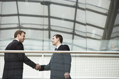 Businessmen Shaking Hands Against Glass Railing Royalty Free Stock Photography