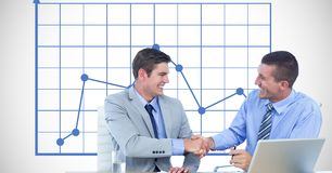 Businessmen shaking hands against graph Royalty Free Stock Image