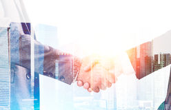 Businessmen shaking hands against large city panorama Royalty Free Stock Images