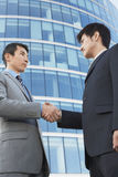 Businessmen Shaking Hands Against Office Building Stock Image
