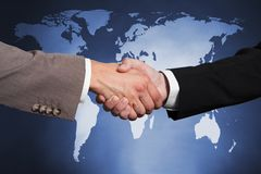 Businessmen shaking hands against worldmap Stock Photos