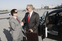 Businessmen Shaking Hands At Airfield Stock Photo