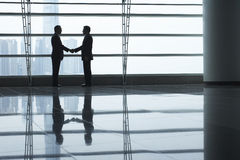 Businessmen Shaking Hands In Airport Terminal. Full length side view of businessmen shaking hands in airport terminal Royalty Free Stock Photos