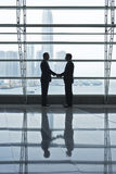 Businessmen Shaking Hands In Airport Terminal Royalty Free Stock Image