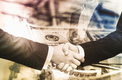 Businessmen shaking hands on background banknotes Royalty Free Stock Images