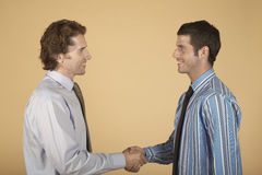 Businessmen Shaking Hands On Colored Background Royalty Free Stock Image