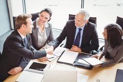 Businessmen shaking hands in conference room Royalty Free Stock Photography