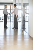 Businessmen Shaking Hands In Corridor Royalty Free Stock Image
