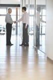 Businessmen Shaking Hands In Corridor Royalty Free Stock Image