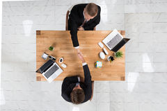 Businessmen Shaking Hands At Desk In Office Royalty Free Stock Photos