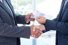 Businessmen shaking hands and exchanging money Stock Images