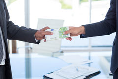 Businessmen shaking hands and exchanging money Royalty Free Stock Images
