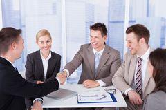 Businessmen shaking hands in front of colleagues Royalty Free Stock Photography