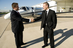 Businessmen shaking hands in front of corporate je. T on ramp Stock Photography