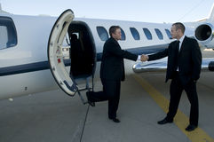 Businessmen shaking hands in front of corporate je. T on ramp Stock Photo