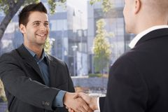 Businessmen shaking hands in front of office Stock Photo