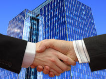 Businessmen shaking hands in front the Skyscraper Stock Image