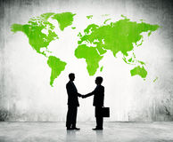 Businessmen Shaking Hands With Green Map Stock Photo