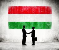 Businessmen Shaking Hands With Hungarian Flag royalty free stock photography