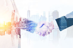 Businessmen shaking hands in large city Royalty Free Stock Photo