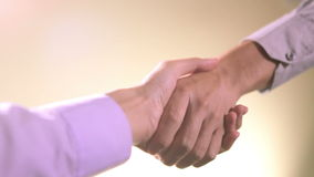 Businessmen Shaking Hands. Light brown background stock video footage