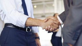 Businesspeople shaking hands. Businessmen shaking hands during a meeting. Closeup of business handshake between two colleagues in a modern office. Successful stock footage