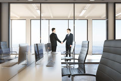 Businessmen shaking hands. In modern business interior. Partnership concept. 3D Rendering Royalty Free Stock Images