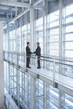 Businessmen Shaking Hands In Modern Office. Full length of businessmen shaking hands by railing in modern office Royalty Free Stock Photo