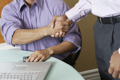 Businessmen shaking hands in office Royalty Free Stock Image