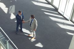 Businessmen shaking hands in office building royalty free stock photo
