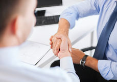 Businessmen shaking hands in office Royalty Free Stock Photos