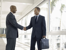Businessmen Shaking Hands In Office Corridor Royalty Free Stock Images